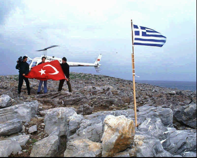 Turkish daily Hurriyet's correspondent Cesur Sert, center, Osman Korkmaz, a cameraman of private TV Channel D, left, and Kemal Suler, a helicopter pilot, on Saturday, Jan.27, 1996 prepare a big Turkish flag to replace the Greek flag placed by Greeks a day before in contested Kardak (Imia) island. Turkey and Greece both claim the tiny deserted piece of land 4.5 miles (7 kms) off the Turkish shore and east of the Greek island Kalimnos. The controversy has resulted in an exchange of protest notes.(AP Photo/Hurriyet, Aykut Firat)